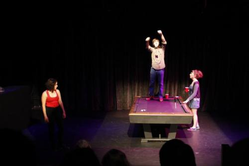 Photo by Robert Schulz SHE (Claire Rigsby) and ALEX (Tatiana Ray) watch as HE (James Henderson) pins a dollar to the ceiling.