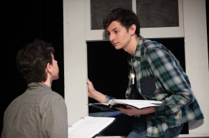The boy (Brad Rizzo) leaves through the window as Dirt (Kevin Hippler) looks on. Photo by Lawrence Peart, courtesy of the University of Texas at Austin