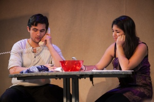 Boomer (Rocket Thrall) makes a call while Marisol (Erica Ayala) checks her phone.  Photo by Lawrence Peart, Courtesy of the University of Texas at Austin